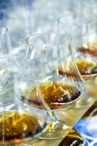 Integration meeting. A glass of alcohol whiskey, cognac or brandy on the table with a blue tint on the table. Soft focus, Macro.