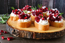Holiday Crostini Appetizers With Cranberries, Pomegranates And Feta Cheese On A Rustic Wood Platter