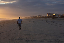 Man Walking On Beach At Sunset