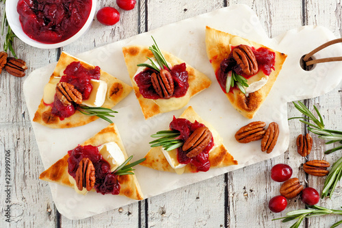 Holiday flatbread appetizers with cranberries, pecans and brie cheese. Above table scene on a white platter.