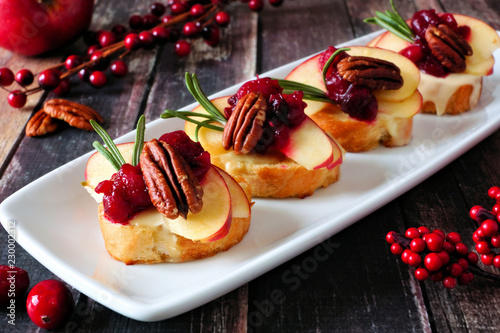 Deurstickers Voorgerecht Crostini appetizers with apples, cranberries, brie and pecans. Top view on a dark slate background.