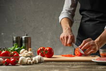The Concept Of Nutrition. The Chef Cuts Tomatoes On The Background Of A Concrete Wall, With Ingredients For Cooking Pizza, Pizza Sauce, Sauce For Italian Pasta