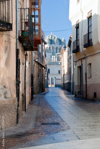 Street zamora with old building on one side and an cathedral in the background