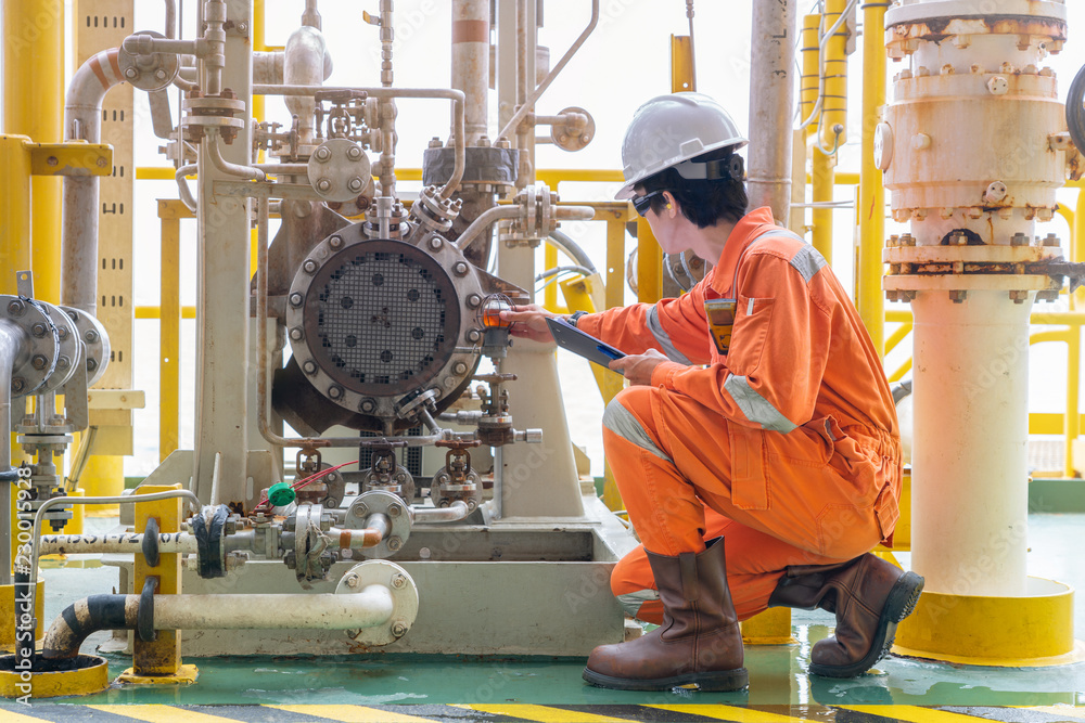 Fototapeta Mechanic inspector engineer check condition of crude oil centrifugal pump and lube oil system at offshore gas central processing platform, power and energy service business industry.