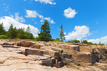 Geological Formation Of Granite Rocks In Acadia National Park, Maine, USA. Landscape With Spruce Forest And Granite Rocks Under A Blue Sky With Cumulus Clouds.
