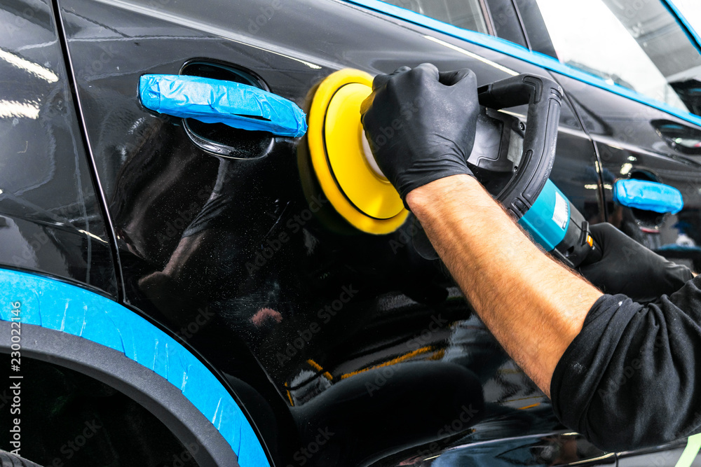 Fototapety, obrazy: Car polish wax worker hands applying protective tape before polishing. Buffing and polishing car. Car detailing. Man holds a polisher in the hand and polishes the car