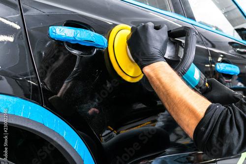 Fotografía  Car polish wax worker hands applying protective tape before polishing