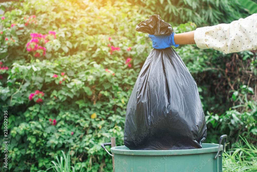 Fototapeta Human hand holding plastic bag in to trash