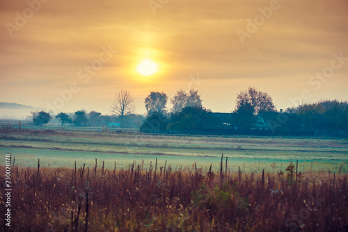 Sunrise over the field in the early misty morning