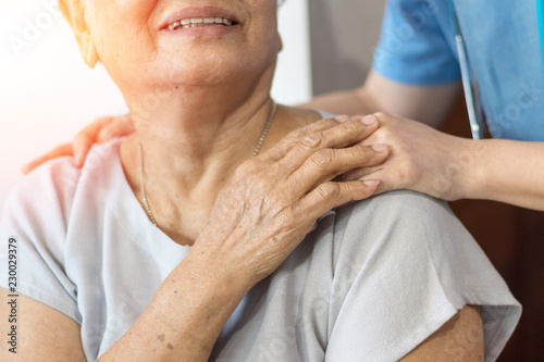 Carta da parati Elderly female hand holding hand of young caregiver at nursing home