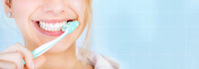 Happy Young Woman Brushing Teeth. Background.