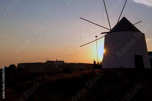Fototapety, obrazy: Sol asomando trás un antiguo molino al atardecer