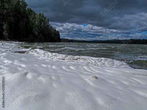 View of the lake from the beach, covered with a large surface of white foam. Unusual summer water landscape. Concept of pollution of nature and a ecology problems of the environment.