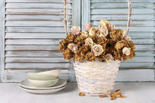 Dried Roses In Basket Against Blinds