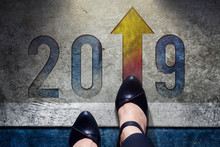 2019 Year Concept. Top View Of Female With Formal Working Shoes Standing On The Floor To Steps Into Number And Forward Arrow