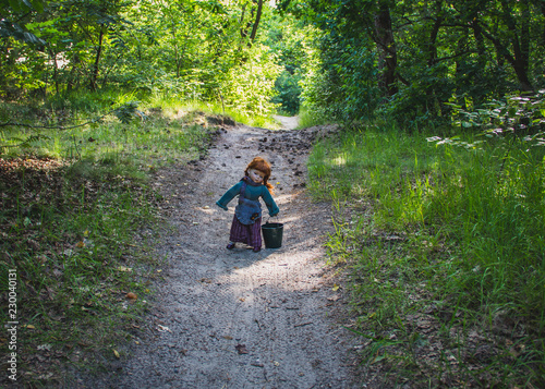 Pippi Longstocking or Cinderella doll in summer forest. Fototapet