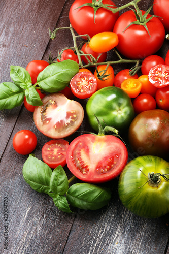 various colorful tomatoes and basil leaves on rustic table.