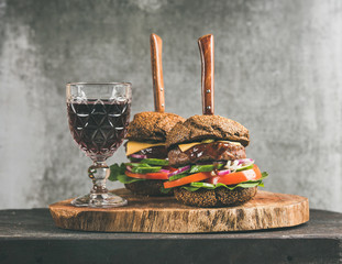 Beef meat cheeseburgers with barbeque sauce and glass of red wine on rustic wooden board, grey concrete wall at background. Comfort food, burger bistro concept