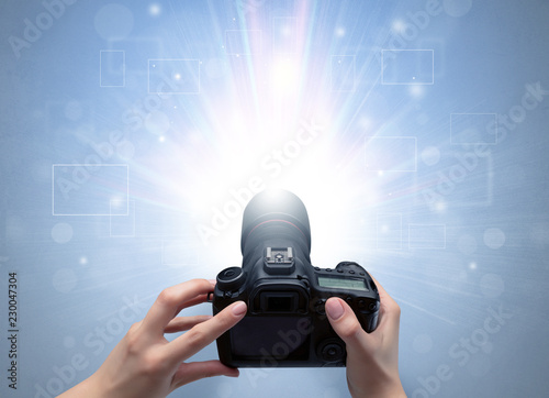 Fotografía  Naked hand taking picture with digital camera and glowing flash concept