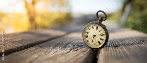 Leinwand Poster Retro Taschenuhr auf Holzbank, Himmel und bunte Blätter im Herbstlicht, Symbol f