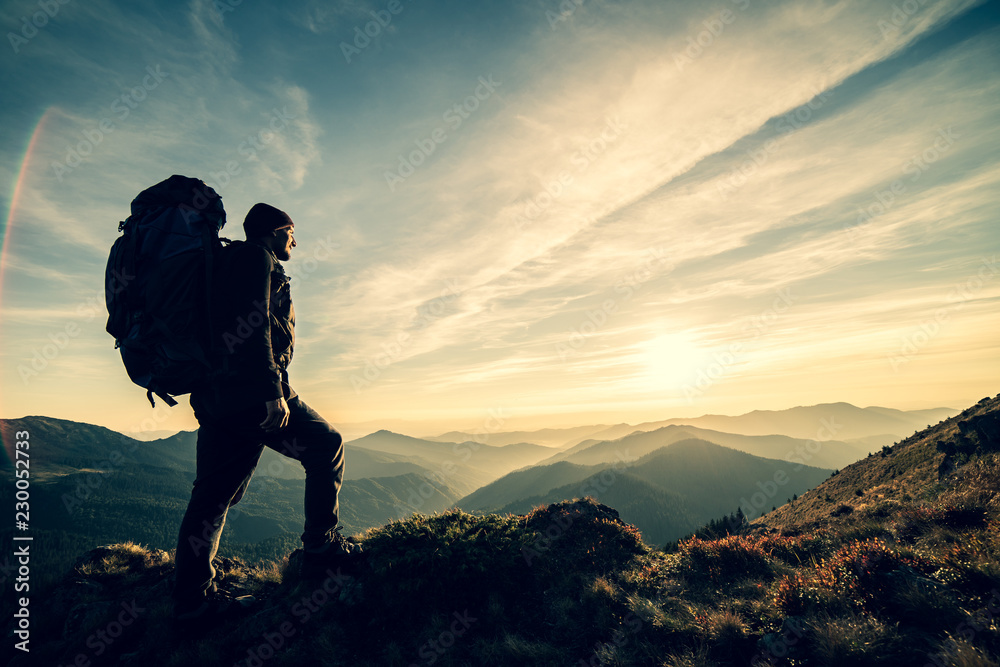Fototapety, obrazy: The man standing with a camping backpack on a rock with a picturesque sunset
