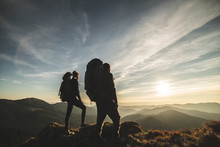 The Couple Standing On A Mountain With A Picturesque Sunset Background