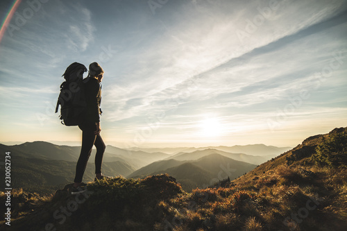 Fotografia  The woman with a camping backpack standing on a rock with a picturesque sunset