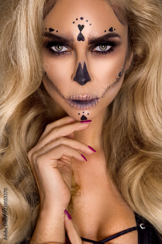 Fototapety, obrazy: Sexy blonde woman in Halloween makeup and leather outfit on a black background in the studio. Skeleton, monster and witch.