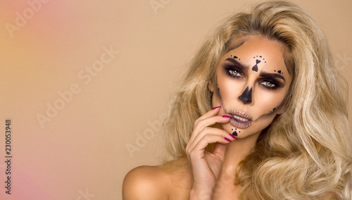Fototapety, obrazy: Sexy blonde woman in Halloween makeup on a beige background in the studio. Makeup artist skeleton, monster, witch.