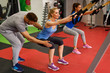 Personal trainer assisting young woman while exercising with trx in the gym