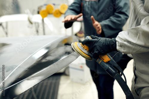 Fotografía  close up, Auto mechanic grinds car part for painting