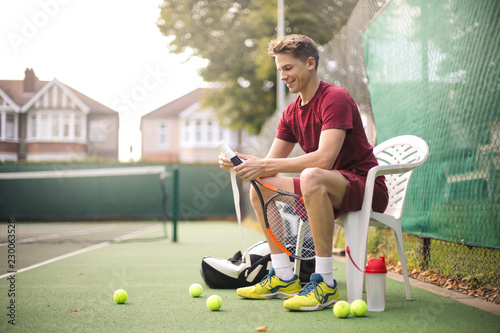 Guy changing the grip of his racket