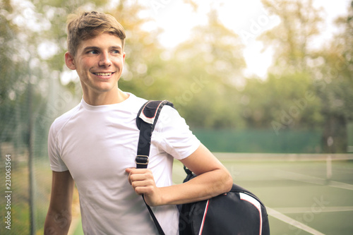 Young guy walking out from a tennis court