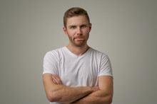 Bearded Guy Frowning Face, Dissatisfied With The Results Of Competition, Holding Hands Crossed, Requires An Explanation Of Why He Loses. Angry Surly Man With Stylish Hairstyle Isolated On White Wall