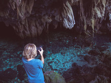 Woman Holding Dlsr Camera Photographing Natural Lake Inside Cave. Colorful Reflection, Turquoise Transparent Water, Summer Adventures. Tourist Destination, Kei Islands, Moluccas, Indonesia.