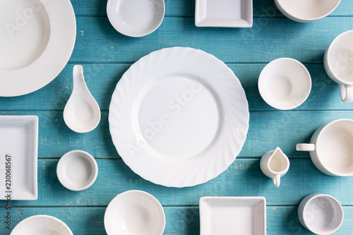 Various empty white plates and bowls on wooden background, Top view