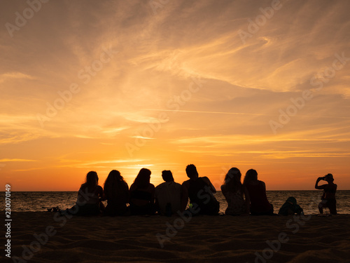 Valokuva  Group of people silhouette on the sunset beach time