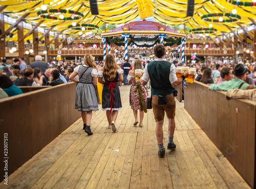 Fototapeta premium Oktoberfest, Monachium, Niemcy. Kelner trzymając piwa, tło wnętrze namiotu