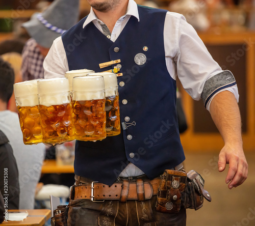 Fotografering Oktoberfest, Munich, Germany. Waiter serving beers, closeup view
