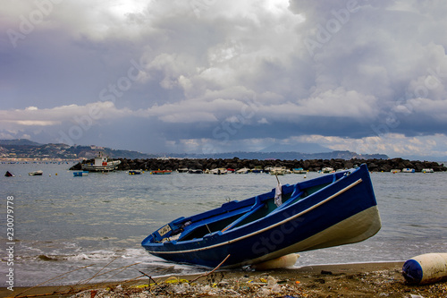Photo Bacoli , barca spiaggiata con Vesuvio in fondo