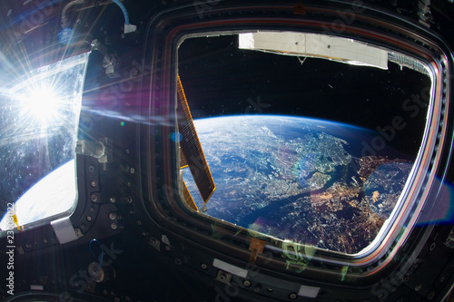 Obraz Collage image with huge NY city at night with city lights from the outer space from the ISS window. Elements of this image furnished by NASA. - fototapety do salonu
