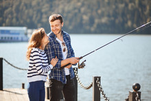 Happy Young Man And His Girlfriend Fishing On Pier In Autumn Lake