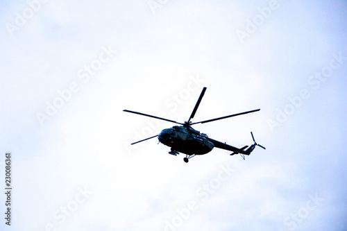 Foto op Canvas Helicopter a large military helicopter hovers in the sky. A camouflaged helicopter flies at high speed.