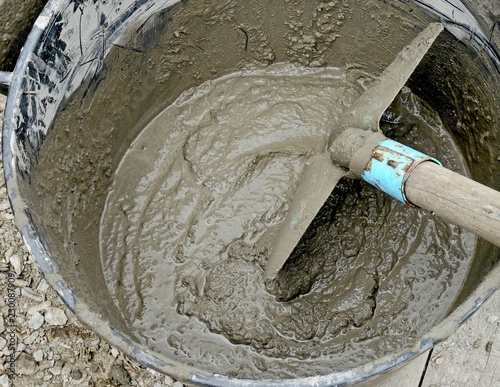 Obraz na płótnie Tools on a construction site: water and cement with shovel in a bucket