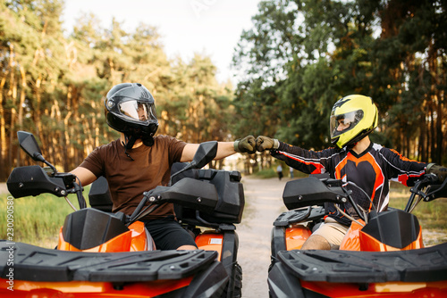 Two atv riders hits fists for good luck, back view
