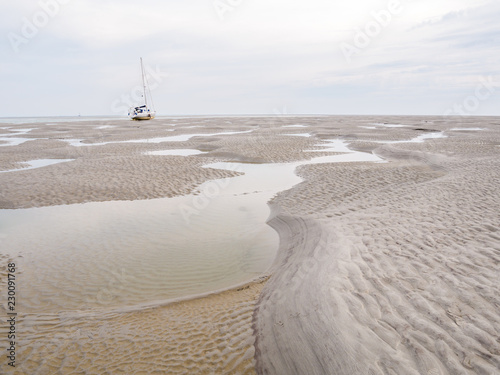 Sailboat dried out on sandflats of tidal sea Waddensea near Boschplaat, Terschel Fototapeta