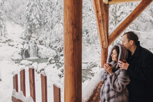 Stylish Couple Holding Hot Tea In Cups And Looking At Winter Snowy Mountains From Wooden Porch. Happy Romantic Family With Drinks Hugging. Space For Text. Holiday Getaway Together.