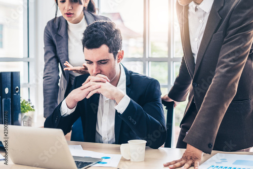 Businessman worry about his job with serious boss discussing while commenting a financial report document at meeting Fotobehang