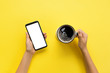 canvas print picture - Female hands holding black mobile phone with blank white screen and mug of coffee. Mockup image with copy space. Top view on yellow background, flat lay
