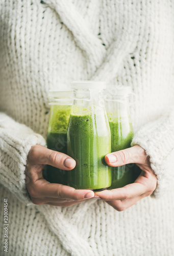 Winter seasonal smoothie drink detox. Female in light knitted sweater holding bottles of green smoothie or juice in her hands. Clean eating, weight loss, healthy dieting food concept